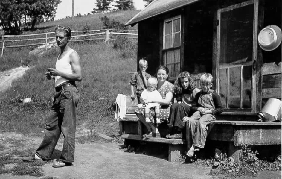 vintage photo of albert stubinsky, his wife and children sitting on front porch of log house