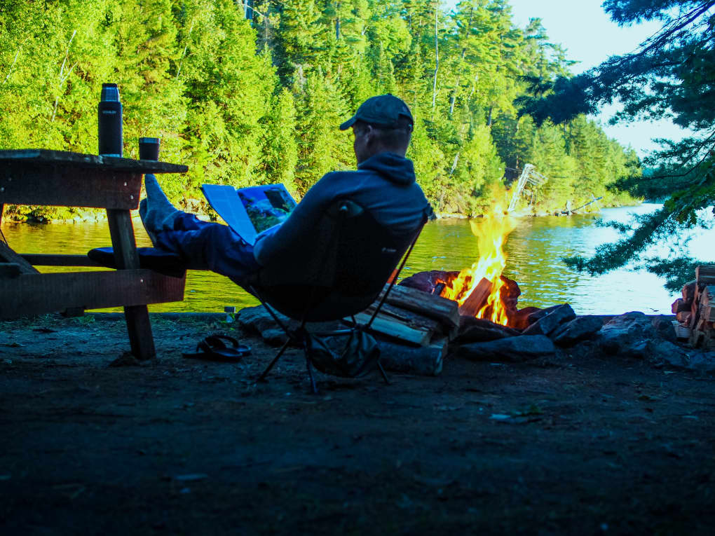 a camper relaxing by the fire and reading a magazine