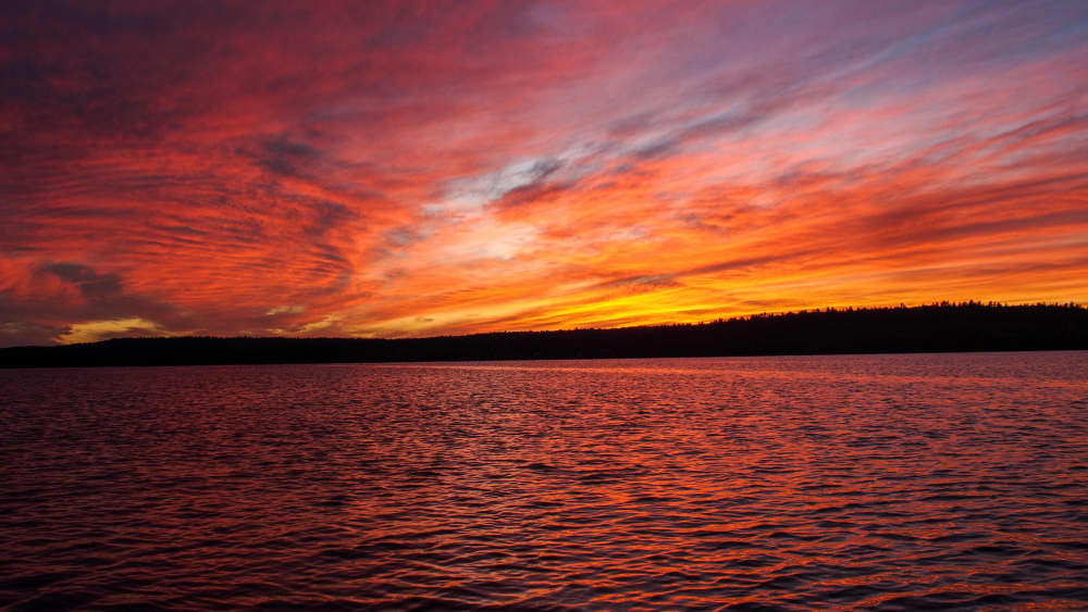 a brilliant red sunset over the lake at black donald tent and trailer park in Ontario Canada