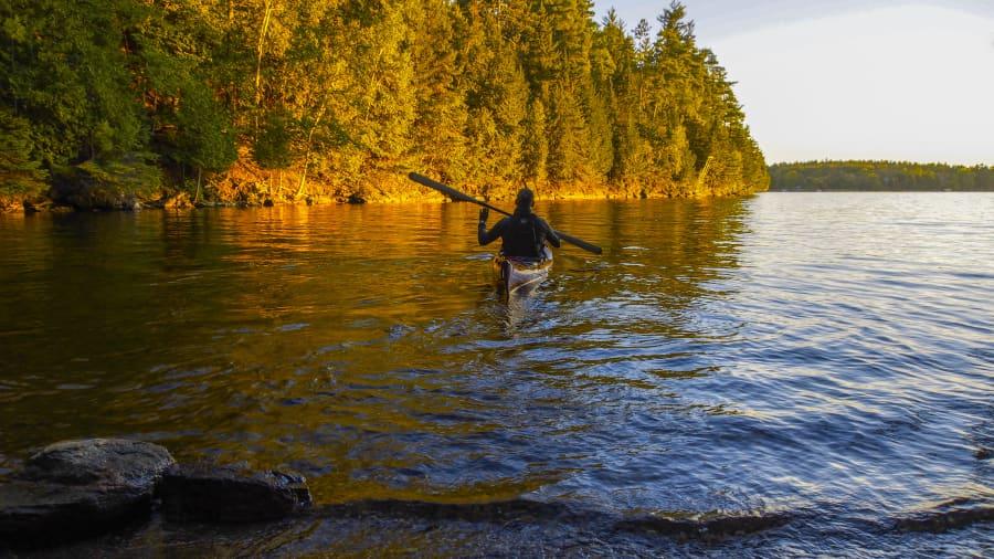 kayaker paddling away from shore at sunset